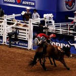The rider is jumping off his bronco onto the Rodeo Clown's horse!